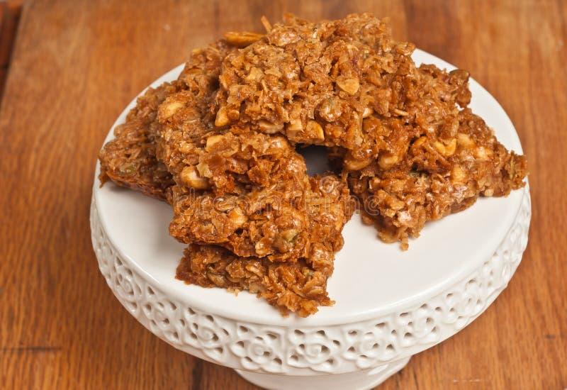Siete cacahuetes recientemente cocidos, barras del coco en el plato blanco de la exhibición foto de archivo