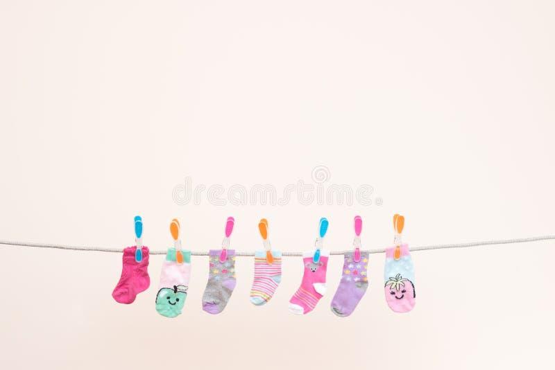 Siete calcetines de los bebés en la línea que se lava paisaje foto de archivo libre de regalías