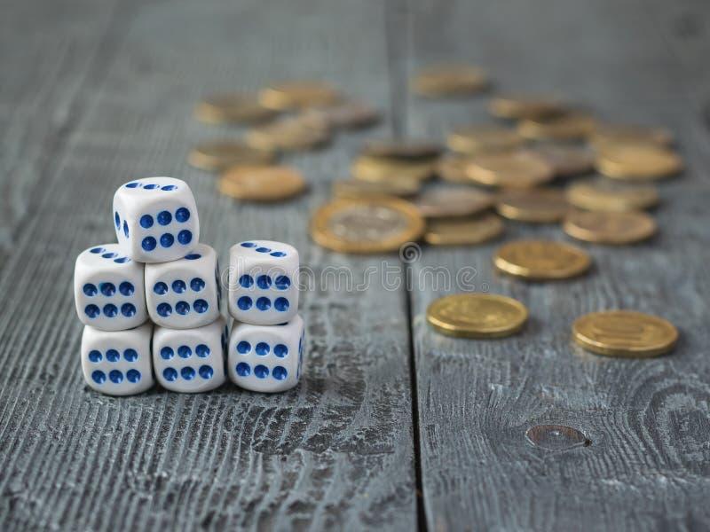 Siete dados y las monedas del metal en una tabla de madera imagen de archivo libre de regalías