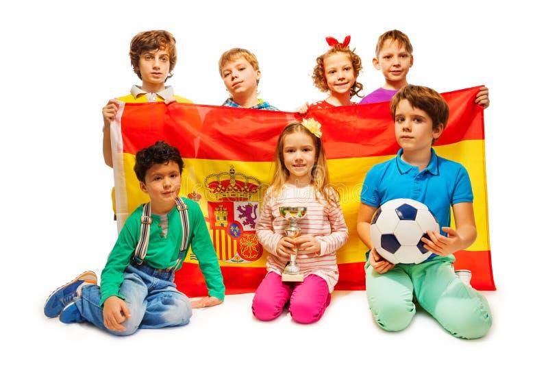 Siete fanáticos del fútbol con la bola que sostiene la bandera española fotografía de archivo libre de regalías