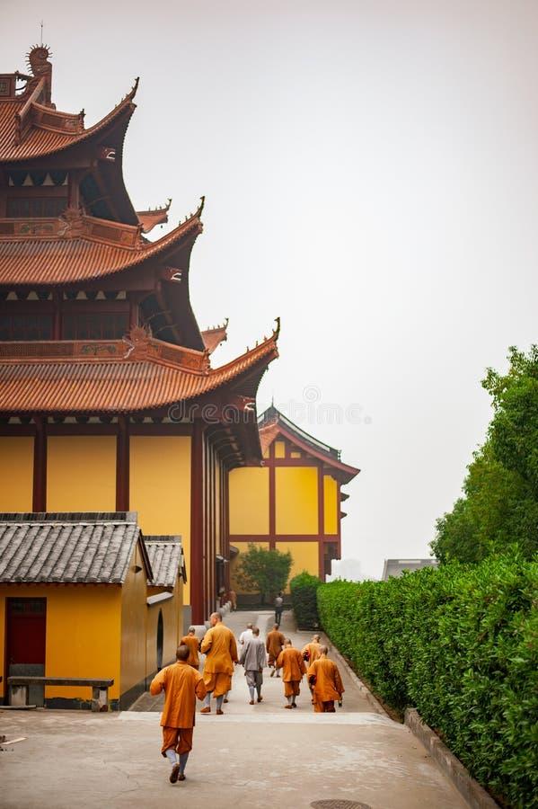 Siete monjes en trajes anaranjados que caminan en Lufeng Temple imágenes de archivo libres de regalías