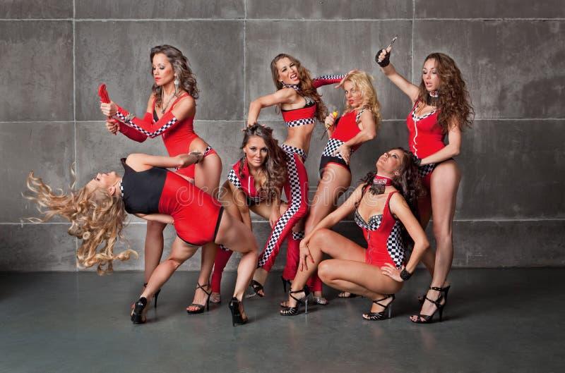 Siete muchachas atractivas go-go lindas en traje que compite con rojo foto de archivo libre de regalías