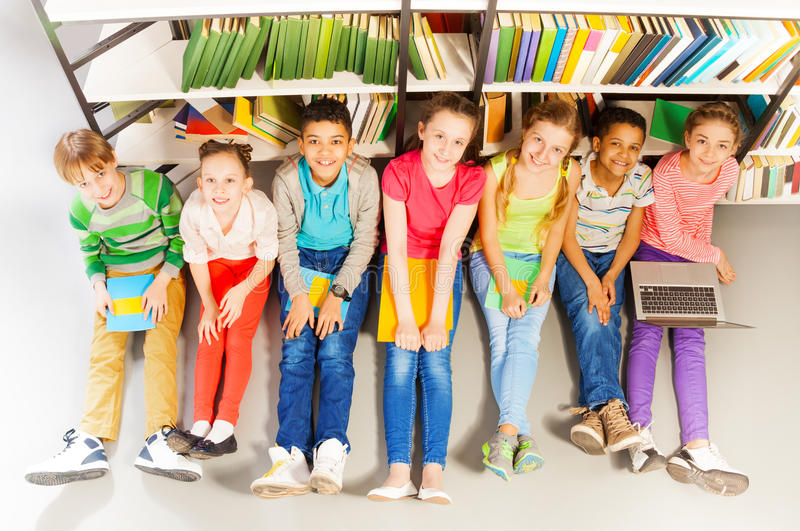 Siete niños sonrientes que se sientan junto en piso fotografía de archivo libre de regalías