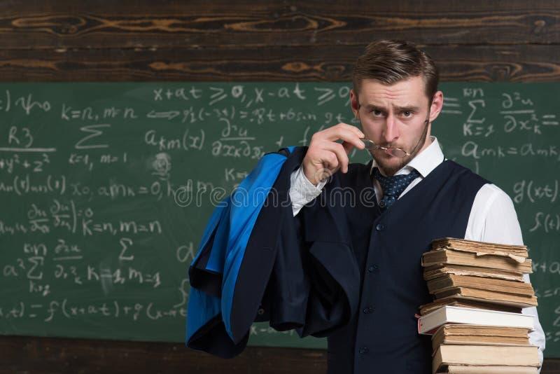 Siete usura convenzionale dell'insegnante serio e sembrare sospettosi, fondo di vetro della lavagna Lavagna in pieno di per la ma fotografia stock