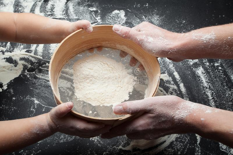 Sieve for flour and hand of woman and child. Mom teaches my daughter to sow flour and cook homemade cakes stock photo