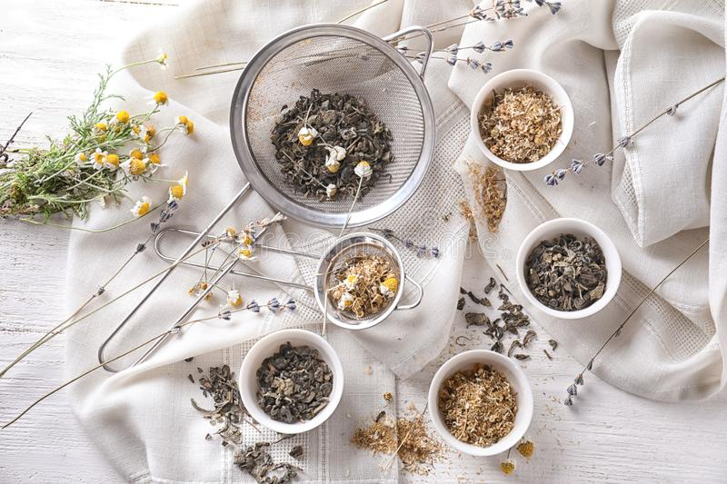 Sieves and bowls with dried chamomile and tea leaves on white table royalty free stock photography