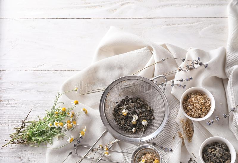 Sieves and bowls with dried chamomile and tea leaves on white table royalty free stock image