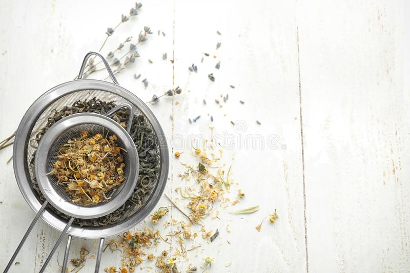 Sieves with dried chamomile flowers and tea leaves on white wooden table stock photos