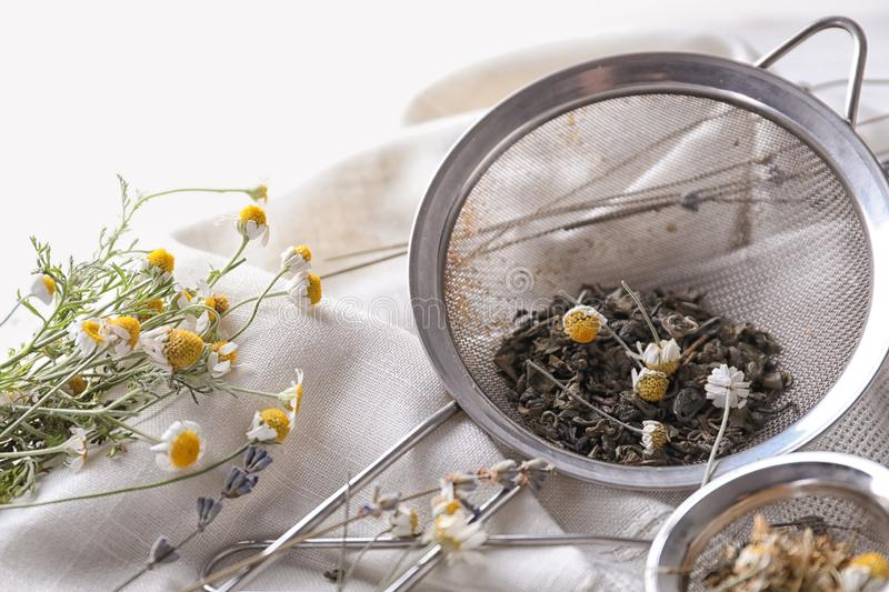 Sieves with dried chamomile and tea leaves on table stock photos