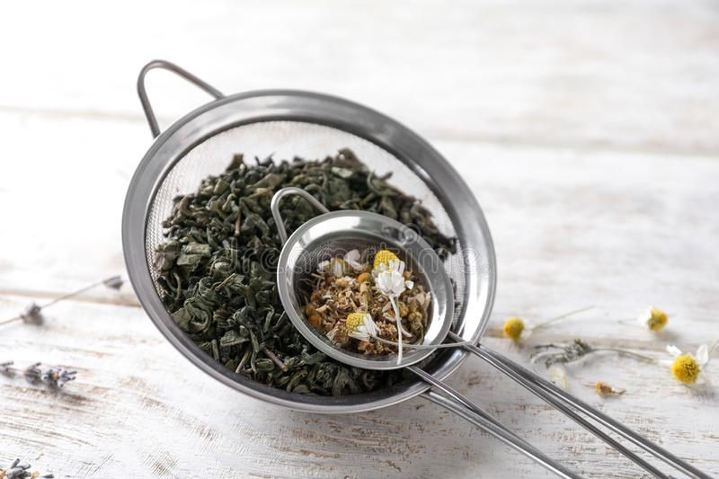 Sieves with dried chamomile and tea leaves on white wooden table royalty free stock photos
