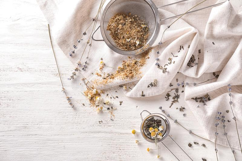 Sieves with dried chamomile and tea leaves on white wooden table royalty free stock photography