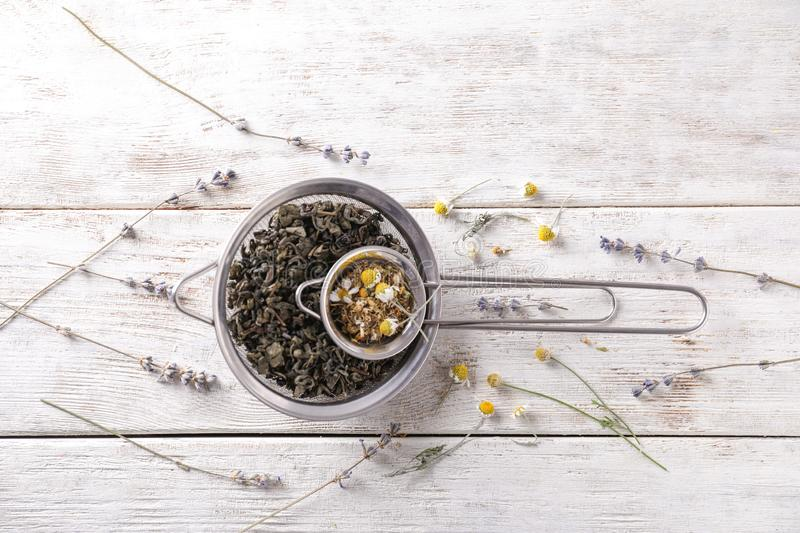 Sieves with dried chamomile and tea leaves on white wooden table stock photo
