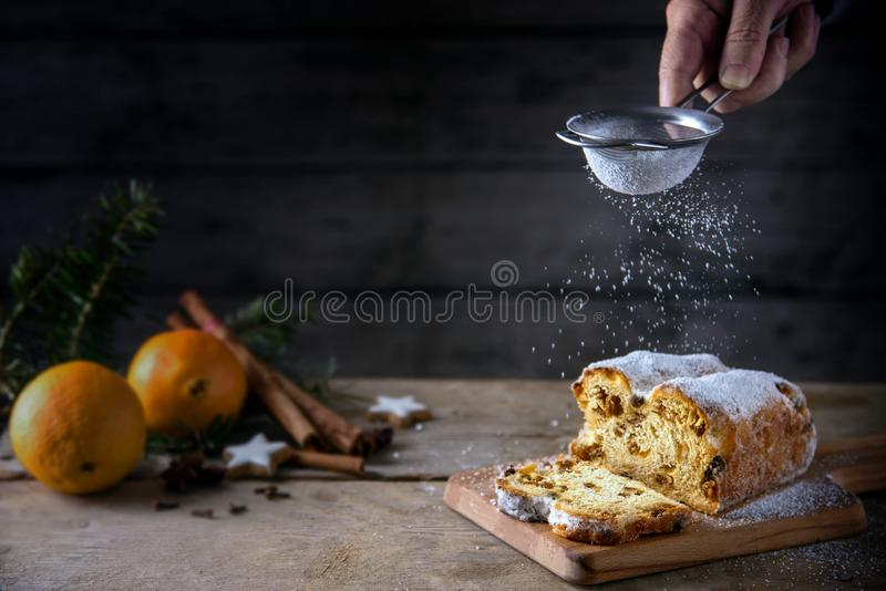 Sieving powdered sugar on a christmas cake, in germany christstollen, orange and spices blurred in the back on a rustic wooden ta royalty free stock images