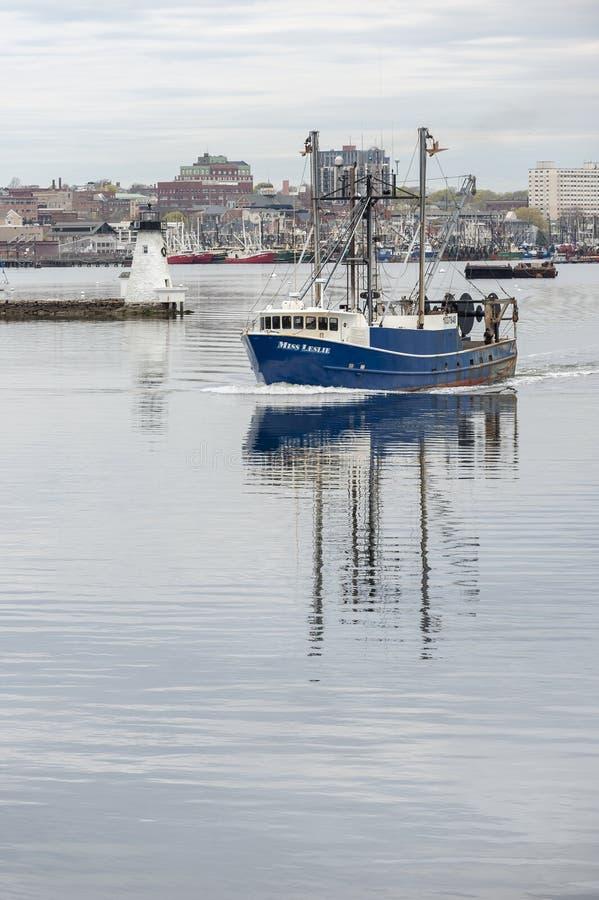 Sig.na Leslie della barca di pesca professionale che passa faro nel porto interno di New Bedford immagini stock