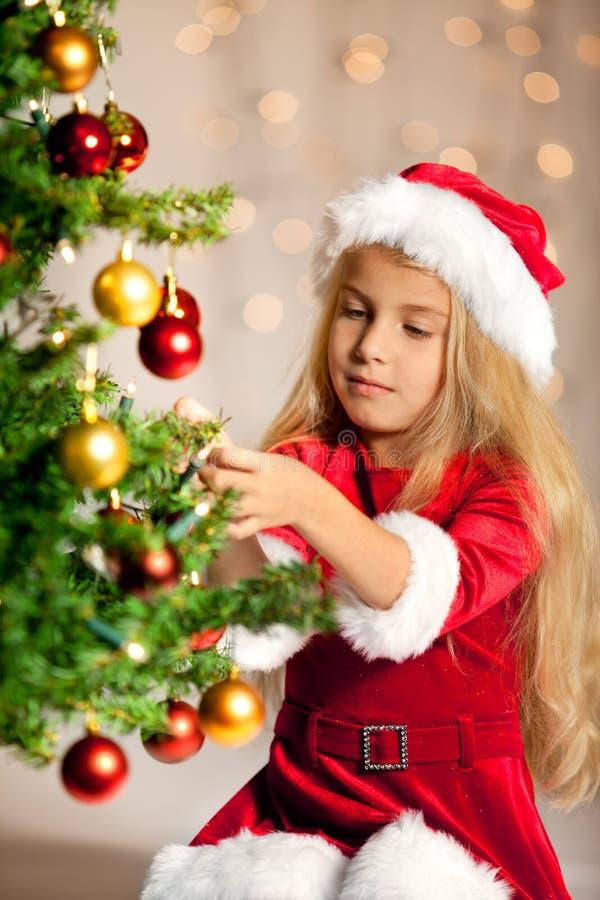Sig.na Santa che decora l'albero di Natale fotografie stock