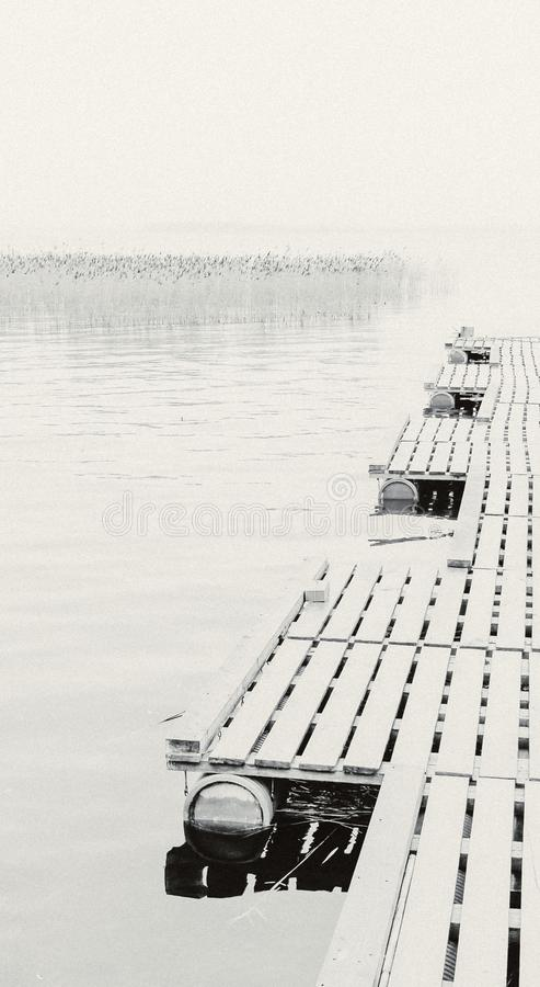 Monochrome view from the dock to the lake on a foggy morning. Sig, Tver region / Russian Federation - April 15 2016: Monochrome view from the dock to the lake on stock photo