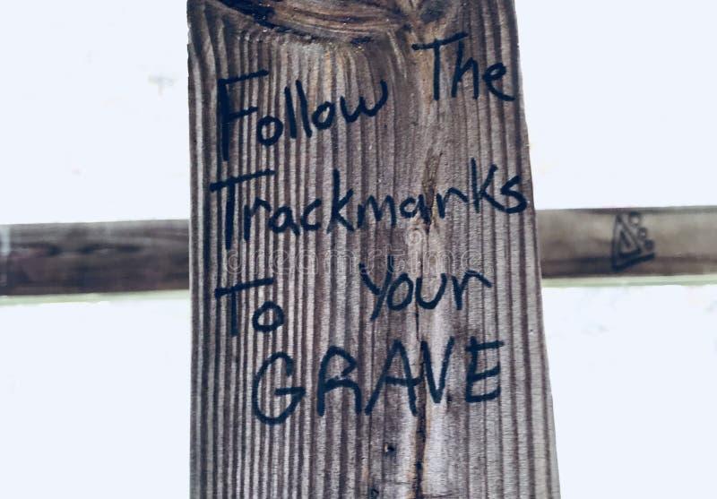Siga as marcas da trilha a seus grafittis da benevolência foto de stock