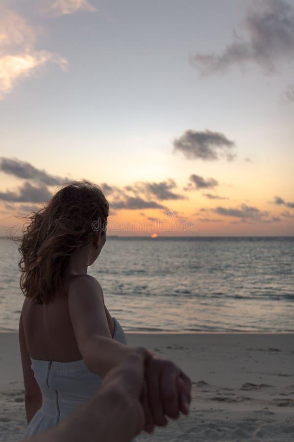 Siga-me conceito da jovem mulher em uma praia que olha o por do sol imagem de stock royalty free