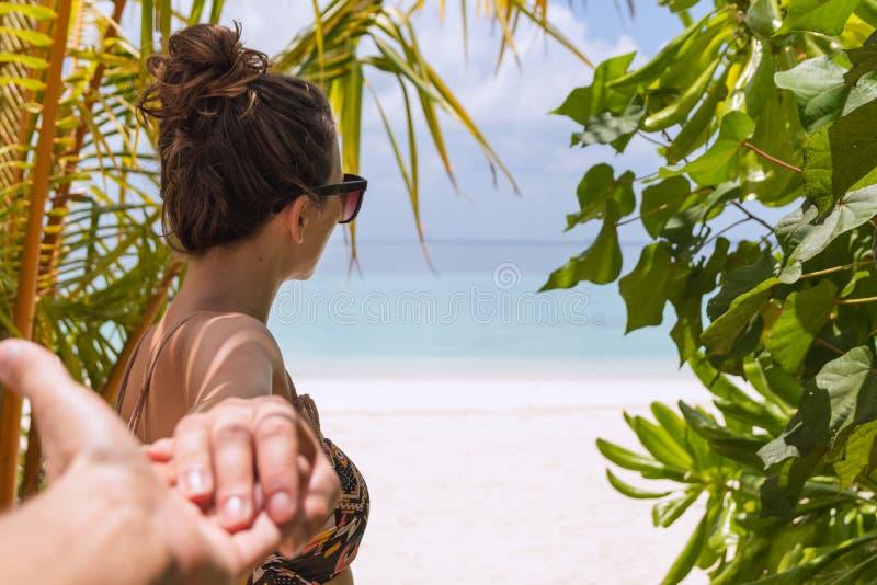 Siga-me conceito da jovem mulher que anda ? praia em um destino tropical fotos de stock royalty free