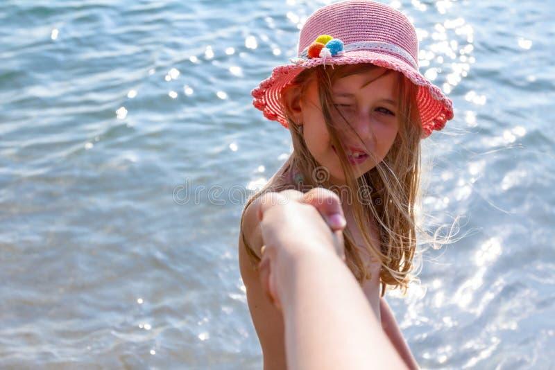 Siga-me A criança no chapéu do verão está puxando e a ` principal s h do pai foto de stock