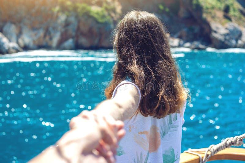Siga-me, a menina moreno atrativa que guarda a mão conduz às montanhas e ao mar azul fotos de stock