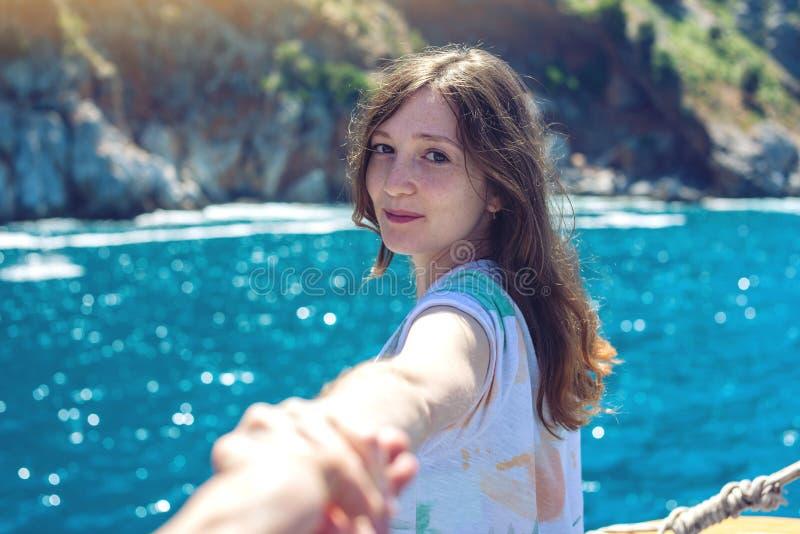 Siga-me, a menina moreno atrativa que guarda a mão conduz às montanhas e ao mar azul fotos de stock royalty free