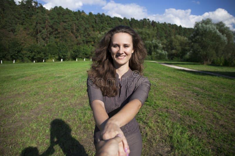 Siga-me, posses bonitas da jovem mulher a mão de um homem fotografia de stock