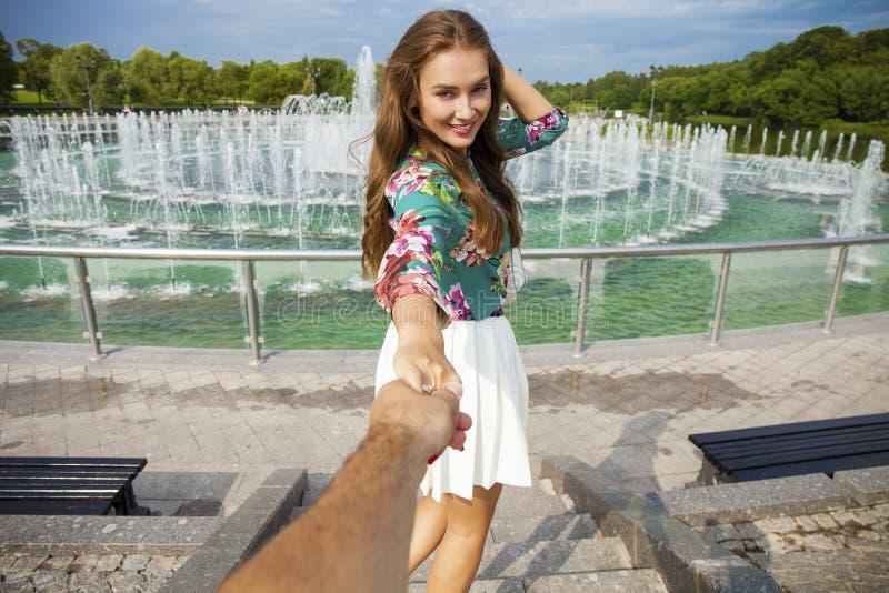 Siga-me, posses bonitas da jovem mulher a mão de um homem imagem de stock
