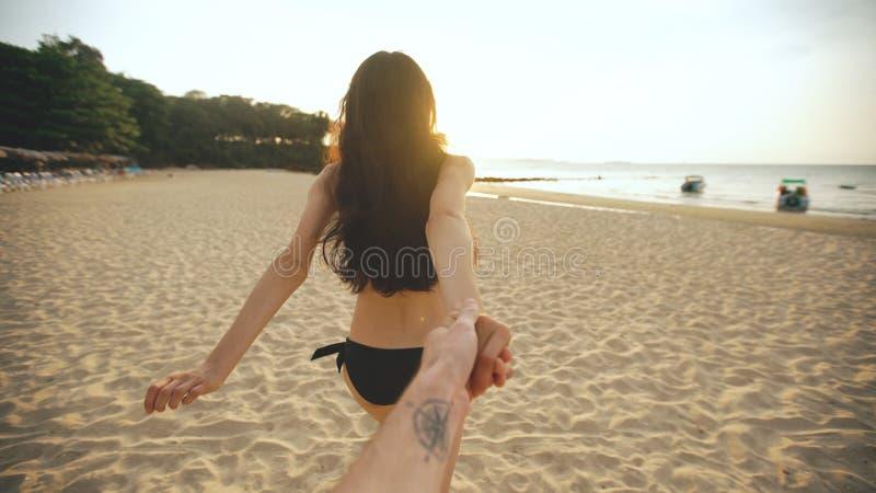 Siga-me tiro da menina 'sexy' nova em um biquini que corre e que guarda a mão do homem na praia no por do sol imagens de stock royalty free