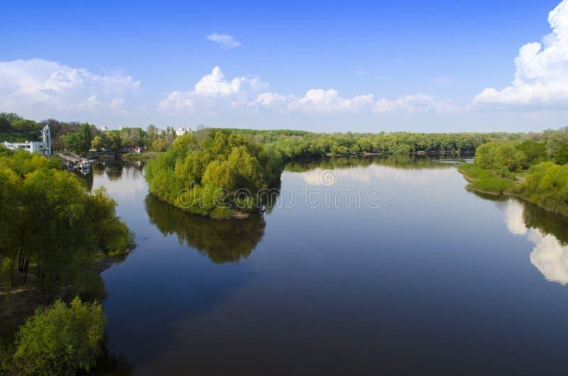 Siga un río ancho con los altos árboles verdes en los bancos contra la perspectiva del cielo azul fotos de archivo libres de regalías