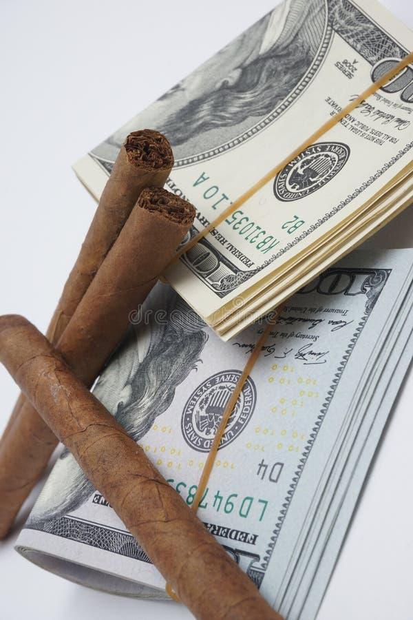 Sigaren en contant geld stock afbeeldingen