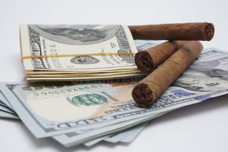 Sigaren en contant geld stock foto's