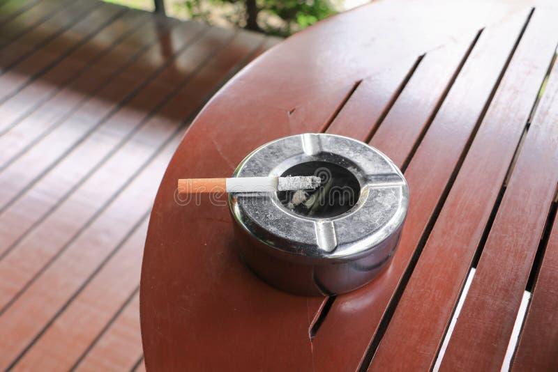 Sigaret in asbakje dat op lijst houten achtergrond wordt geplaatst royalty-vrije stock foto