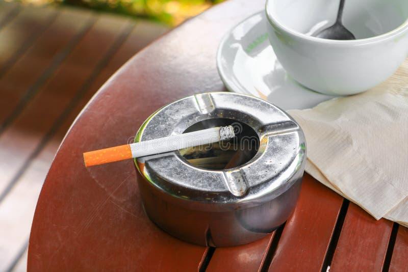 Sigaret in asbakje dat op lijst houten achtergrond wordt geplaatst stock fotografie
