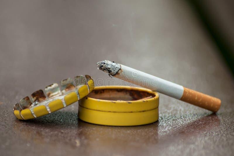 Sigaret op metaalzakasbakje op houten lijst royalty-vrije stock foto