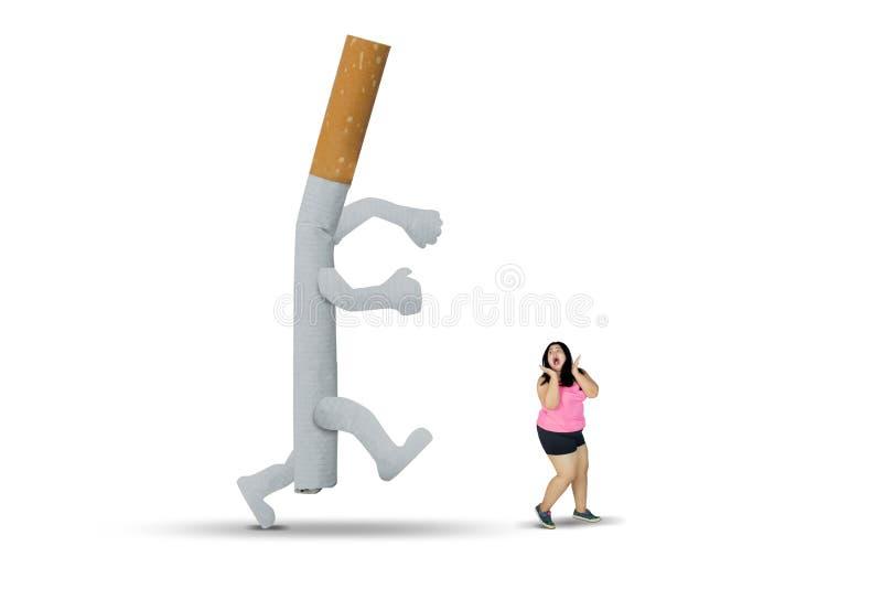 Sigaretta che insegue donna grassa sullo studio immagine stock