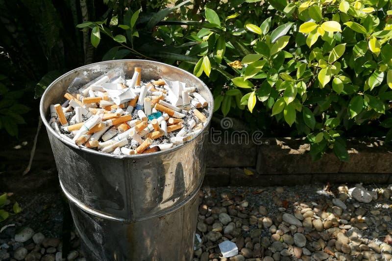 Sigaretta dei lotti sulla sabbia in recipiente davanti alla toilette fotografie stock