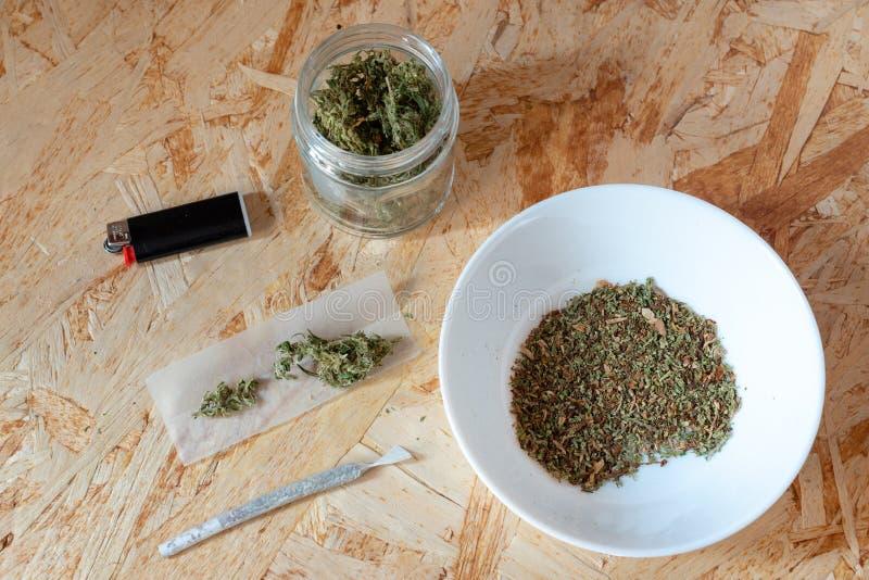 Sigaretta di marijuana, prodotta con le cime della canapa, la carta di rotolamento e l'accendino, uso illegale della sostanza nar immagini stock