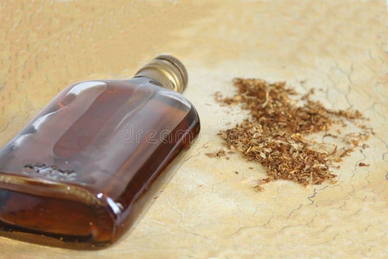 Sigaretta, tabacco e bottiglia immagine stock