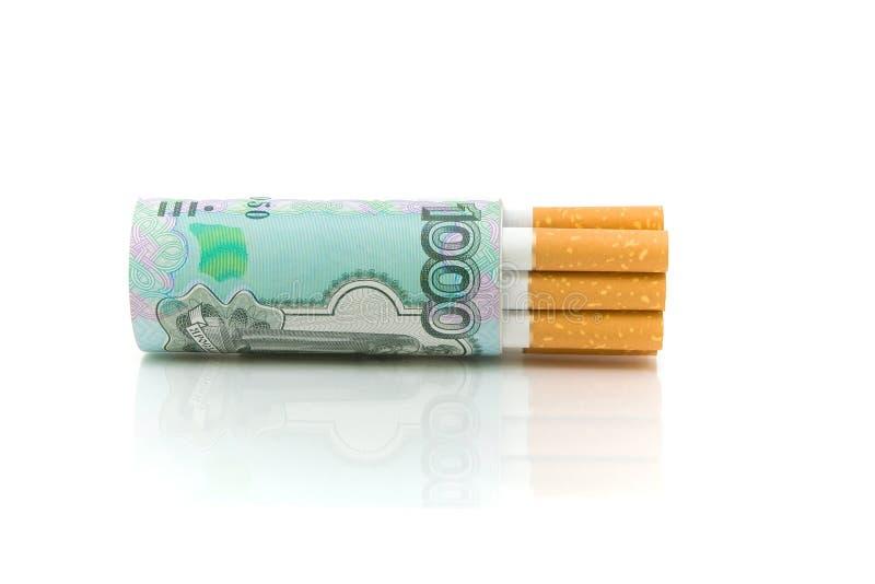 Sigaretten en geld op een wit close-up als achtergrond stock fotografie