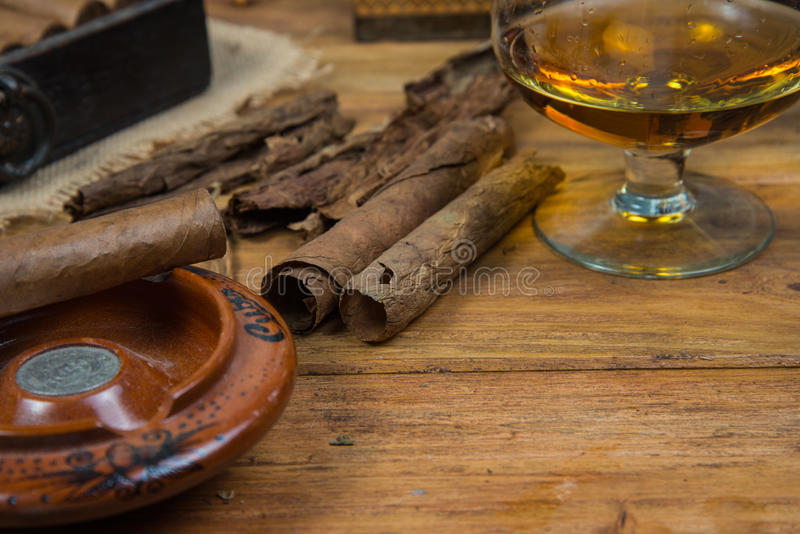 Sigari e rum o alcool sulla tavola fotografie stock