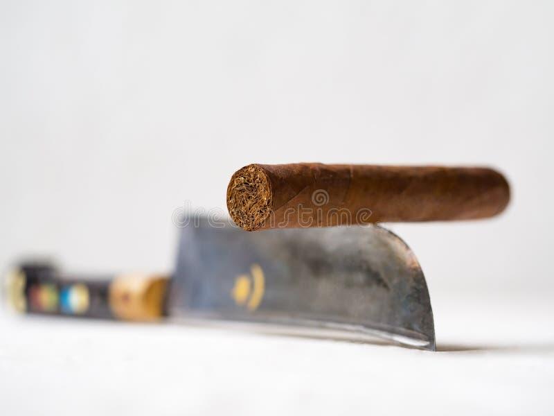 Sigaro che equilibra su un bordo di coltello Fumo dei pericoli immagini stock libere da diritti