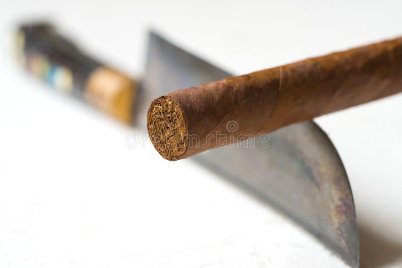 Sigaro che equilibra su un bordo di coltello Fumo dei pericoli fotografia stock