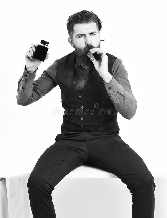Sigaro di fumo dell'uomo barbuto con il fronte serio, tenente profumo fotografia stock