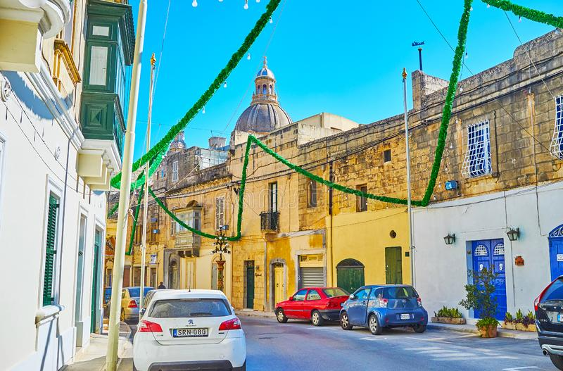 The winding streets of Siggiewi, Malta. SIGGIEWI, MALTA - JUNE 16, 2018: The narrow winding street, decorated with bright festival garlands with a view on the stock photo