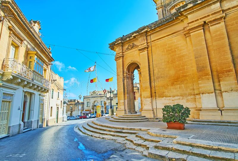 City walk in Siggiewi, Malta. SIGGIEWI, MALTA - JUNE 16, 2018: San Nikola street of old town with a view on historic mansions with flags in square in front of St royalty free stock photos