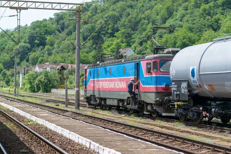 SIGHISOARA, ROMANIA - 1° LUGLIO 2016: Il capotreno sale la locomotiva del treno con i vagoni del carico alla stazione ferroviaria fotografia stock libera da diritti