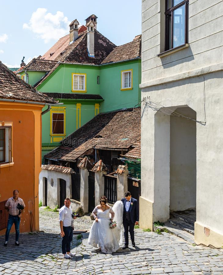 Sighisoara, Romania – 2019.    Happy newly married couple preparing to take a picture stock image