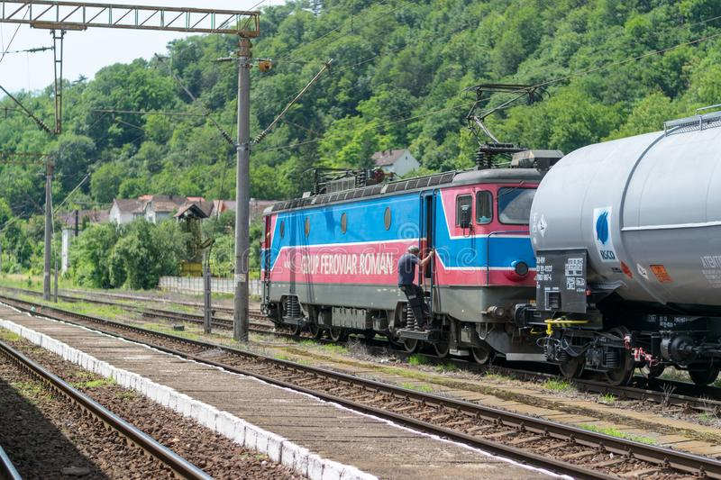 SIGHISOARA, ROMANIA - 1 JULY 2016: Train conductor get on the train locomotive with cargo wagons at the Sighisoara train station i royalty free stock photo