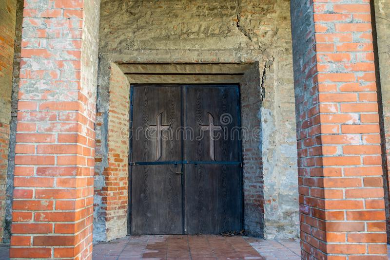 Medieval lutheran church entrance, brick pylons, hand carved cross on the door. stock image